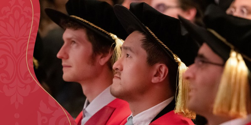 There is a red block of colour to the left of several graduates wearing convocation robes and hats in profile to the right.