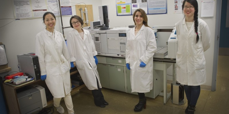 Four women wearing white coats standing in a laboratory.
