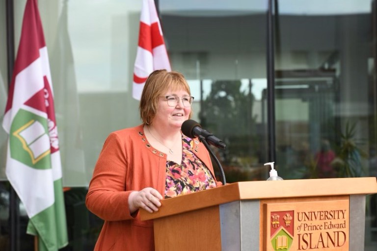 Dr. Margaret Steele, Dean of the Faculty of Medicine, Memorial University, stands at a lecturn and smiles.
