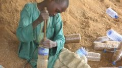 child packing sand into bottle for bottle house