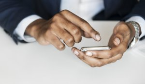 A hand holding a cell phone with the other hand about to touch the screen.