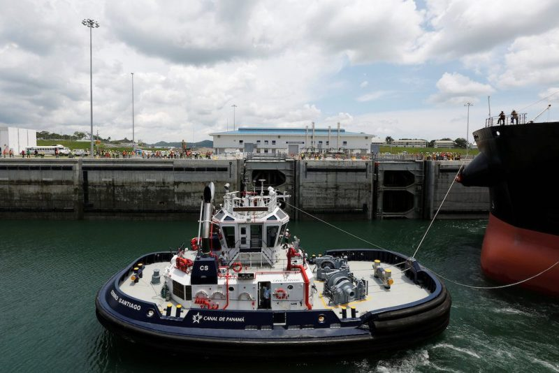 A tugboat drags a Post-Panamax cargo ship during the first trial run at the new sets of locks on the Atlantic side of the Panama Canal, in Panama City, Panama June 9, 2016. REUTERS/Carlos Jasso