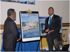 President of GCCI, Clinton Urling (right) and Prime Minister, Samuel Hinds after unveiling the fourth edition of the Business Guyana Magazine