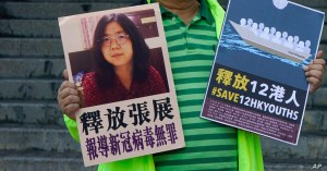 FILE - A pro-democracy activist holds placards with the picture of Chinese citizen journalist Zhang Zhan outside the Chinese central government's liaison office, in Hong Kong, Dec. 28, 2020
