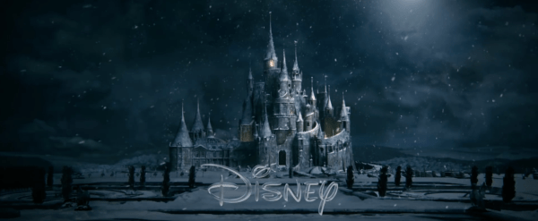 The Beauty and the Beast castle on a dark and snowy night with the disney logo in front of it