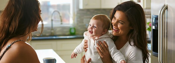 Two women smiling with a cute baby which they may have because of SIMS IVF and the family planning services they provide.