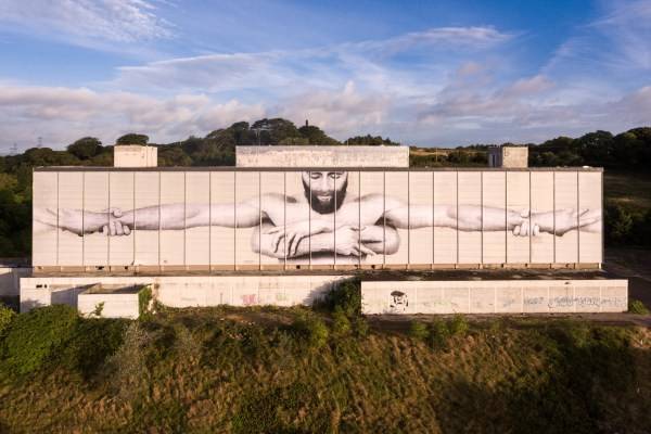 Joe Caslin's new mural on the back of a hotel in waterford showing a bearded man holding arms around him and supported by another pair of arms from behind