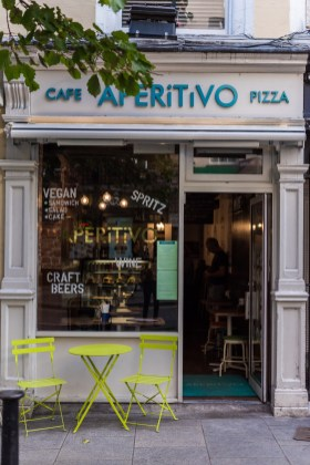 A portrait photo of Aperitivo on Parliament street from the outside, with green table and chairs on the street