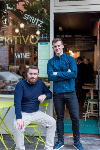 Renan and Paul Keville sitting and standing outside Aperitivo