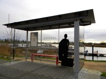 The silhouette of a woman with a suitcase at a bus shelter as part of Will St Leger's Out of the shadows art project