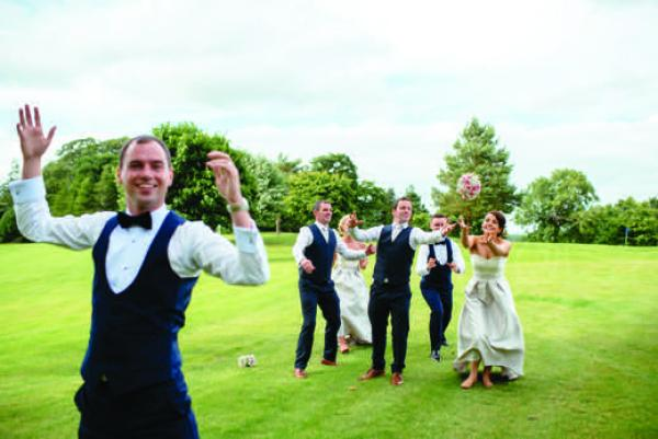 The groom throwing a bouquet with men and women trying to catch it on grass from Andrew and Thomas' Real Weddings article