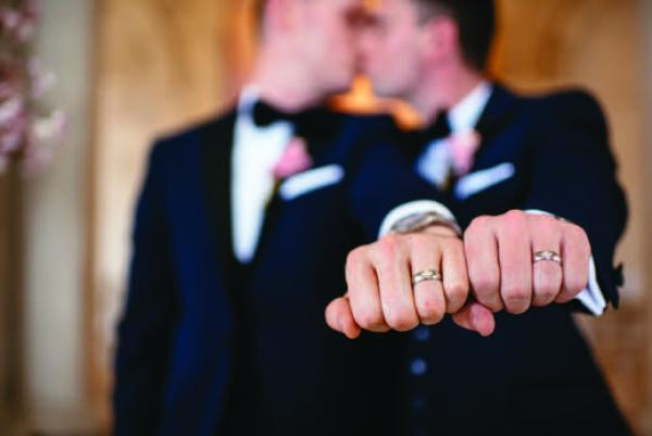 Thomas and Andrew's ring fingers in a fist showing off their rings from Andrew and Thomas' Real Weddings article