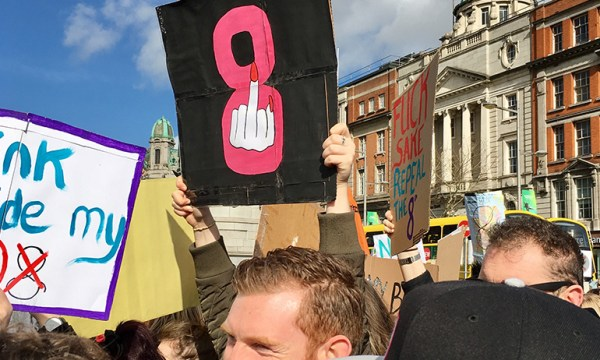 A Strike 4 Repeal sign with a middle finger over a pink 8
