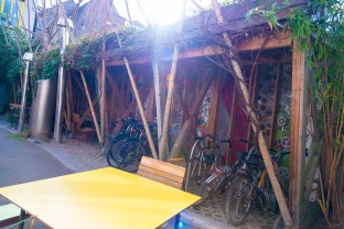 A yellow table, wooden chair and bike rack outside with the sun beaming down at the cake cafe and slice which are both owned by Ray O'Neill