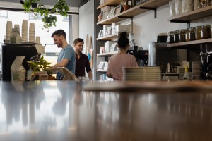 Three people standing in Two Boys Brew café