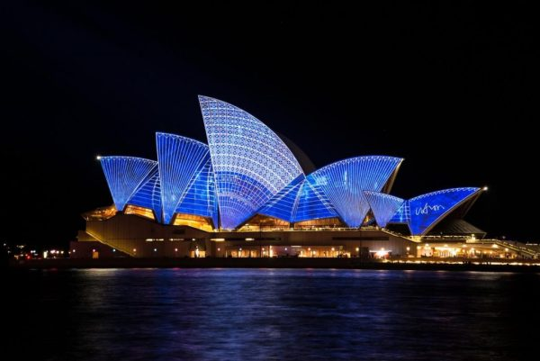 an image of sydney opera house at night illuminated in blue to indicate that an Irish diaspora vote from emmigrants in Australia might impact elections