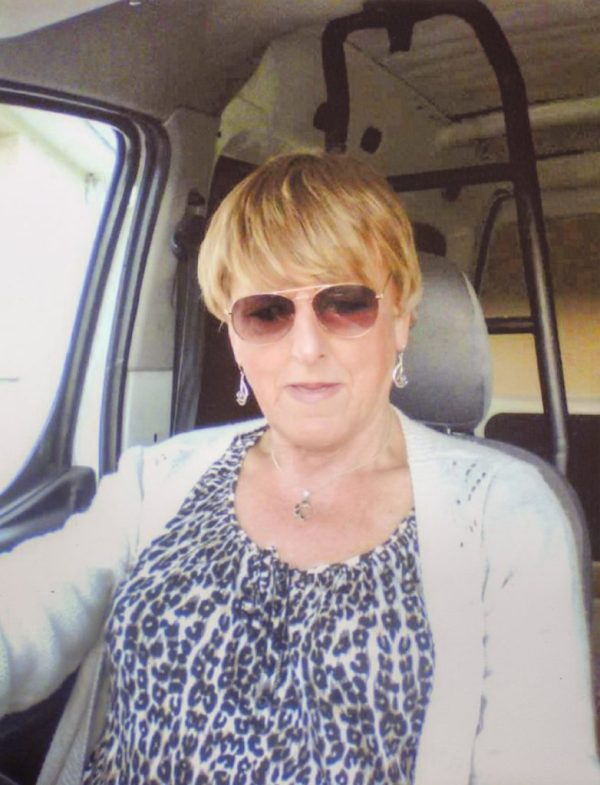 Christine Beynon from the art exhibition in Becoming Christine sitting in a car with sunglasses on