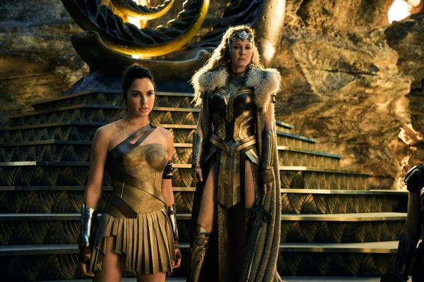 Wonder woman standing in golden clothes with another woman
