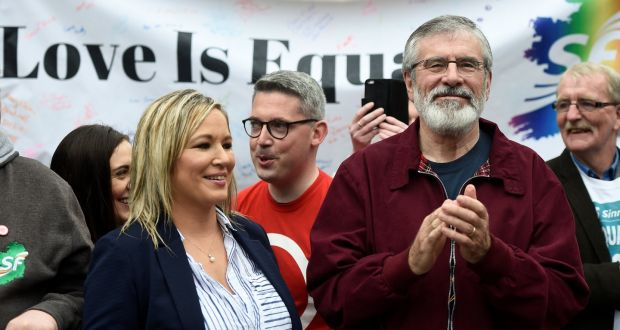 Gerry adams claps his hands in front of a banner reading 'love is equal'
