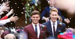 Tom Daley and Dustin Lance Black in a still frame from their wedding video walking in wine and navy suits with confetti in the air