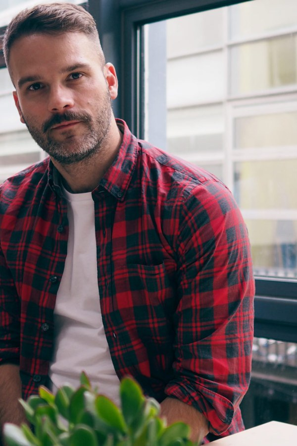 Kris Nelson sitting in a red flannel shirt and who is pro march for choice