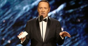 Kevin Spacey standing in a tux with cards in one hand
