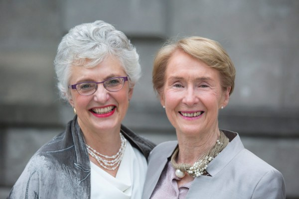 Katherine Zappone and her wife Ann Louise Gilligan, who won a lifetime achievement award at The GALAS 2017, smiling in front of a grey stone background