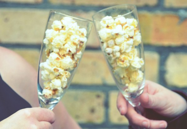 Cornude popcorn in champagne glasses against a brick wall background