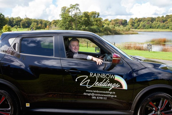 Daragh Doyle sitting in his black rainbow weddings themed car in front of a green grassy area and a lake