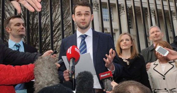 A man stands talking to a crowd of reporters, gesturing with his left hand.
