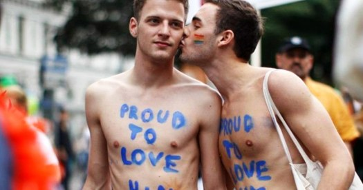 "Two men at Austria Pride with ""proud to love him"" enscribed on their chests celebrate Marriage Equality"