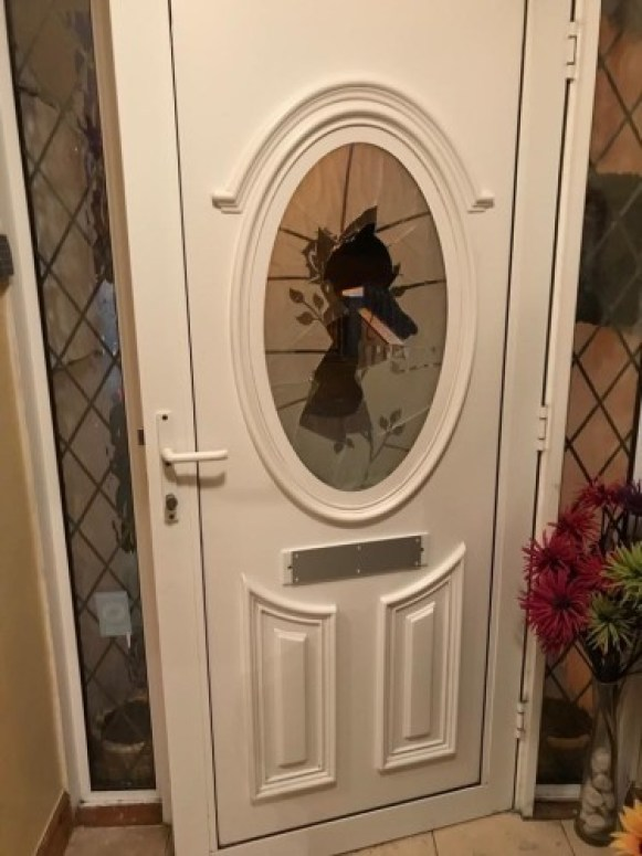 A photo of Franci Timmons front door. The glass in the center has been smashed in. The letterbox has been sealed up, most likely in an attempt to prevent hate mail.