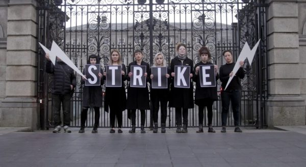 Image of woomen dressed in black standing outside leinster house with a strike banner