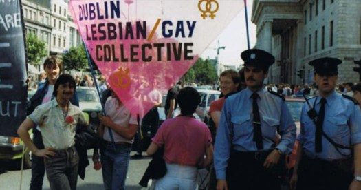 Famous photo of the Dublin Lesbian/Gay Collective in the 1980's. Two members hold a banner as the garda look on