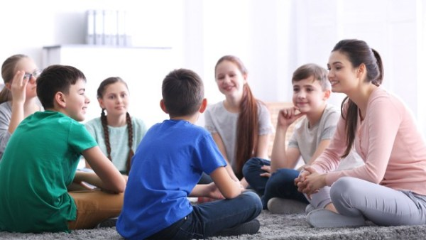 Volunteer sits with a number of teenagers in a circle