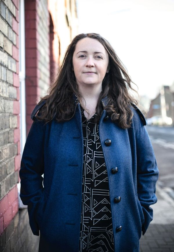 Journalist and writer Una Mullally standing in a streets, with her hands in her pockets
