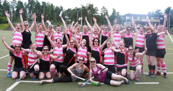 Pink Ladies hockey team posing in group shot on the pitch