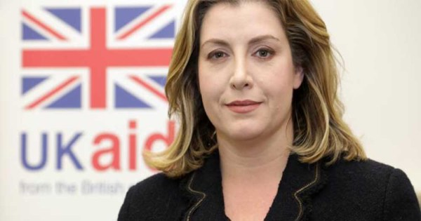 Minister Penny Mordaunt with a UK flag in the background