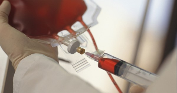 A syringe injecting blood into a plastic bag