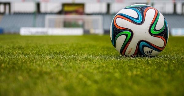Rainbow soccer ball sits on a field
