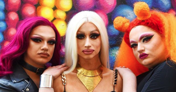 Three drag queens in full makeup posing against a multi coloured wall