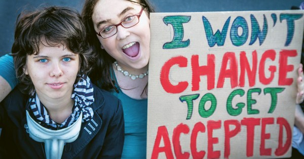 """Two transgender people hold a sign that says """"I won't change to get accepted"""""""