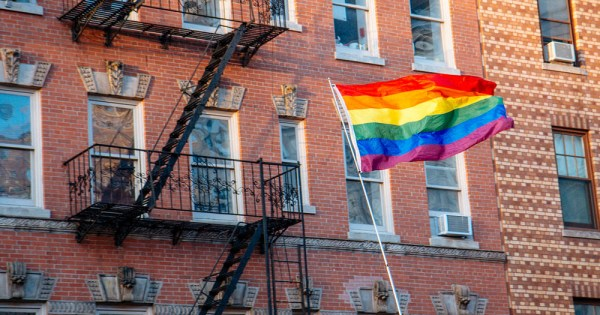 LGBT+ rainbow flag flied in front of an apartment block direct provision