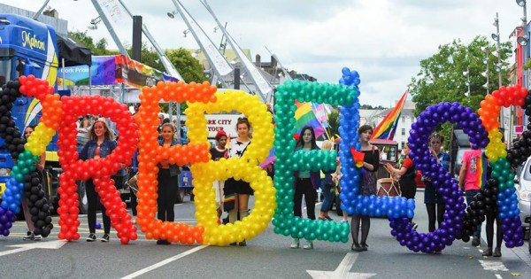 A group of people at Cork Pride holding rainbow coloured balloons which spell out REBELS