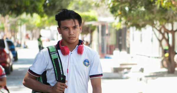 A still from the film 'Dario' competing for the Iris Prize showing a young man walking down a sunny street with a backpack slung over his shoulder