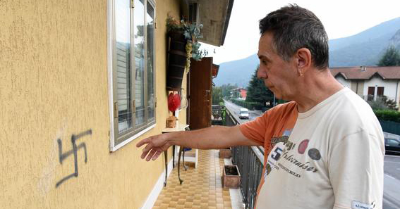 One of the victims showing a swastika graffiti outside his house in Verona