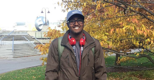 Image of Mahad Olad standing outside on a college campus.