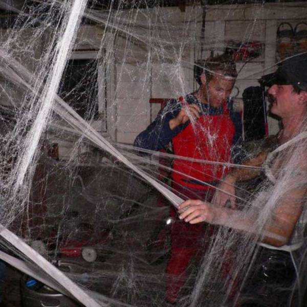 People tangled in cobwebs during a Halloween party