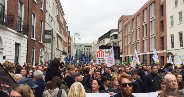 Hundreds of people fill the street outside Leinster House holding up banners in protest of the housing crisis