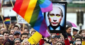 A crowd of LGBT+ supporters are gathered, a rainbow flag is in the foreground and a poster of Russian leader Putin wearing make-up is seen in the background